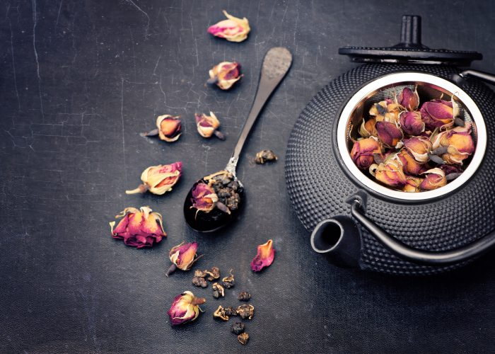 Green tea with flowers roses in cast-iron kettle. Asian style